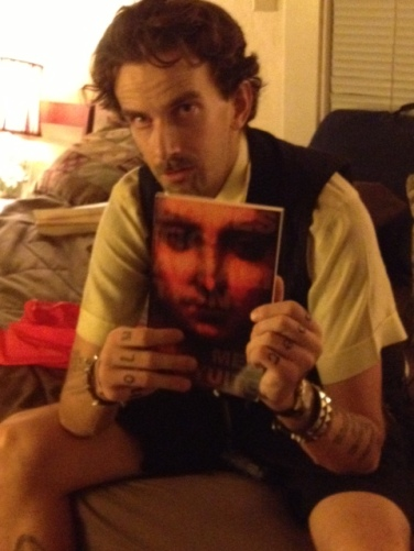 Author Isaac Kirkman holding Meg Tuite's Domestic Apparitions